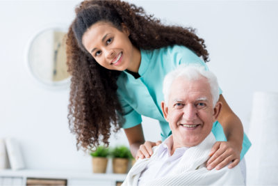 caregiver and elderly man in a wheelchair