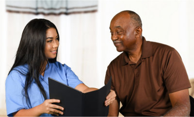 caregiver showing document to elderly man